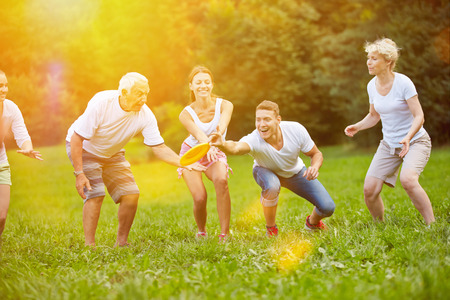Familia feliz jugando al frisbee juntos en el jardín en verano Foto de archivo