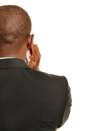 Personal security from behind with hand on a headset in the ear Stock Photo