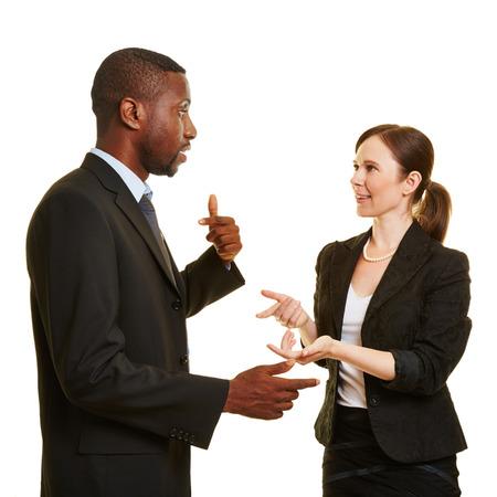 Afrikaanse man en blanke vrouw met elkaar praten als ondernemers