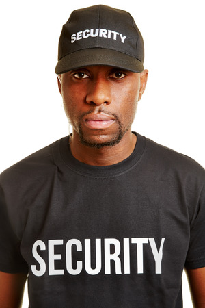 usher: Black man from security firm with basecap and t-shirt