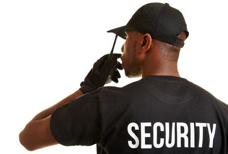 seguridad en el trabajo: Guardia de seguridad negro con aparato de radio desde atrás