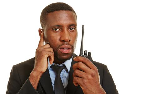 Zwarte bodyguard met hoofdtelefoon en radio werken voor persoonlijke veiligheid Stockfoto