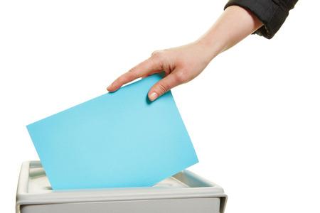 Vrouwelijke hand beslissende stem bij de verkiezing met stembiljet in doos