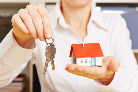 key handover: Hands of a woman holding two keys and a small house