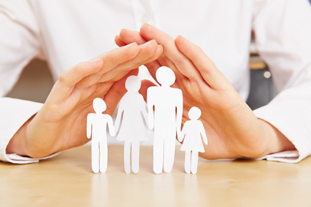 Female hands protecting family with children made of paper Stock Photo