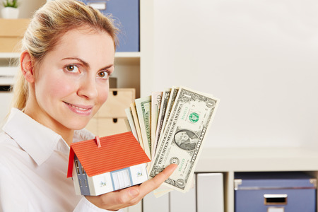 sell: Smiling woman as real estate agent with small house and Dollar bills