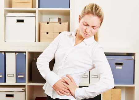 hip pain: Business woman in office with back pain standing and holding her hip