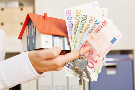 household insurance: Hand of a woman with house and Euro money and door keys