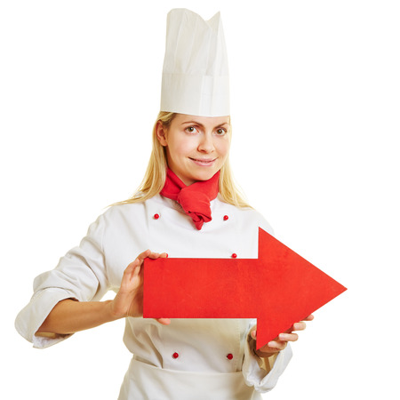 apprenticeship: Smiling female cook in apprenticeship holding a big red arrow to the right Stock Photo