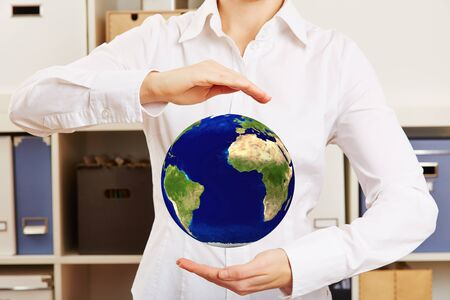 hovering: Business woman holding hovering world globe in her hands