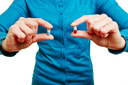 pangs: Hands of a woman comparing two different medical pills