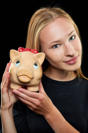 thrift box: Young blonde woman holding a big piggy bank in her hands