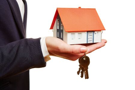 renter: Real estate agent holding small house and keys in her hand