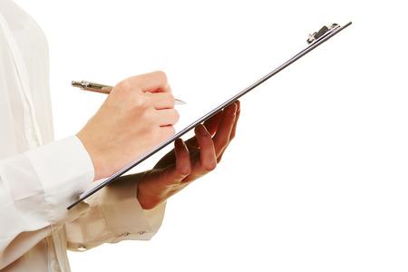inventario: Mano de una mujer llenando lista de comprobación en un sujetapapeles