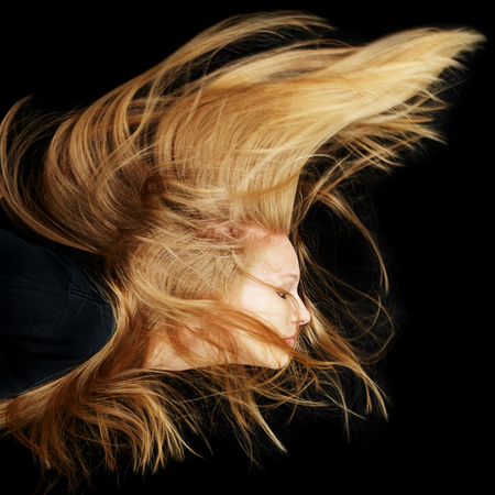 flying hair: Young attractive woman with long blonde flying hair at night
