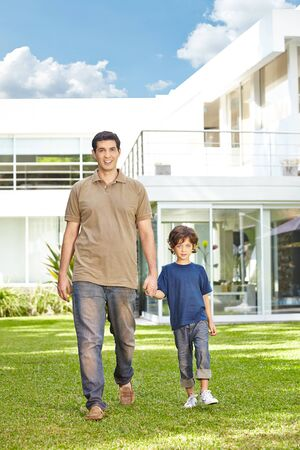 family outside: Father and son walking in front of a house in the sun