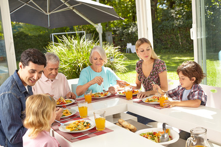 family together: Happy family in three generations eating lunch together in summer