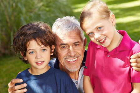 grandkids: Grandfather with two happy grandkids in a green garden