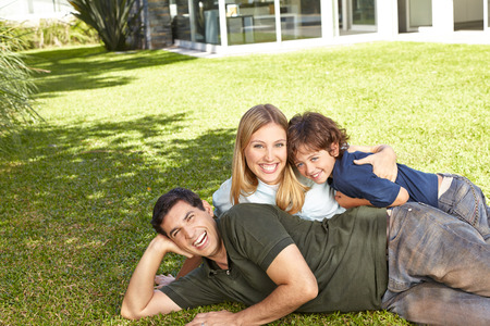 home and garden: Happy family laying with son in garden in summer Stock Photo