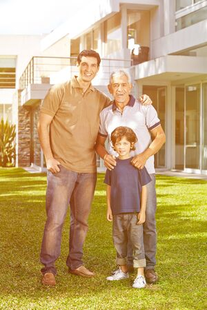 generation: Family with grandfather and grandchild in front of a house in the garden