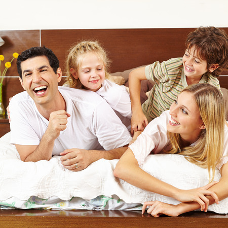 family tickle: Two children tickling their parents in bed in the morning Stock Photo