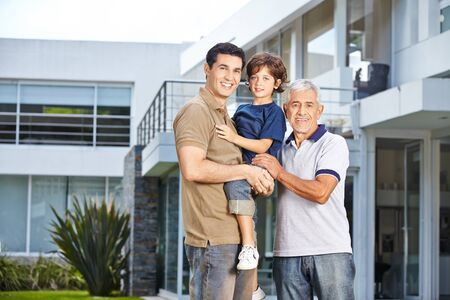 family outside: Family with father, son and grandfather in front of a modern house