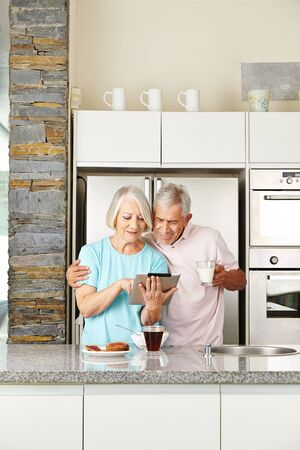 happy senior: Senior couple with tablet computer in kitchen at breakfast