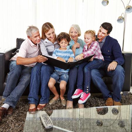 Gezin met kinderen en grootouders kijken naar een foto album samen in een woonkamer