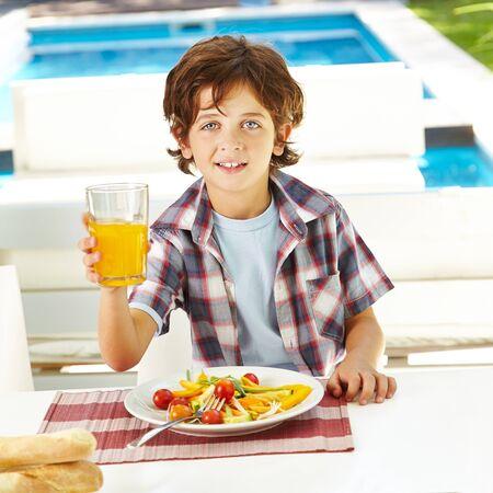 tomando jugo: Niño feliz comiendo ensalada y beber jugo de naranja en el almuerzo