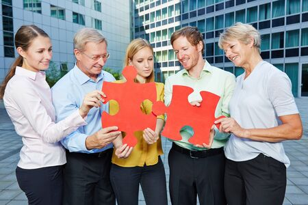 business puzzle: Business people team solving a big jigsaw puzzle together in teamwork