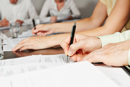 writes: Hand signing contract in business meeting after negotiation Stock Photo