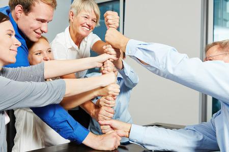 Business mensen bouwen toren met hun vuisten in een teamwork inspanning
