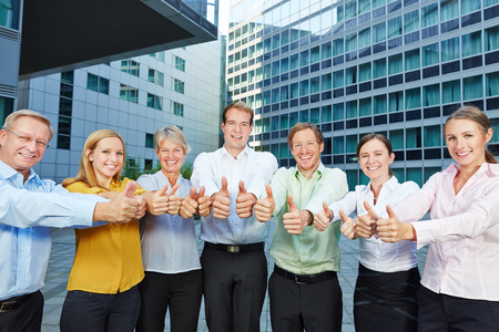 thumbs: Successful group of business people holding many thumbs up