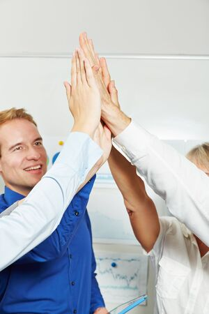 hands high: Businesspeople clapping hands to give high five in the office Stock Photo