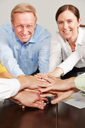 team hands: Teamwork in a business team with stacked hands as symbol Stock Photo