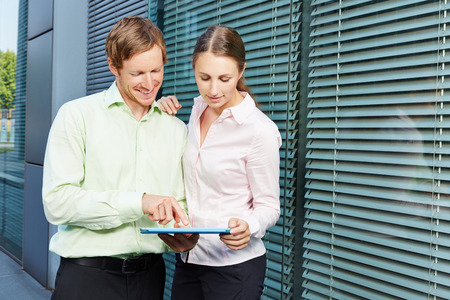 Online Business: Two business people with tablet computer watching video streaming online Stock Photo