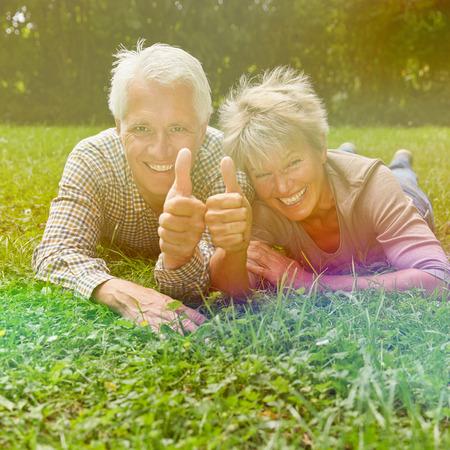 congratulate: Happy senior couple holding thumbs up to congratulate Stock Photo