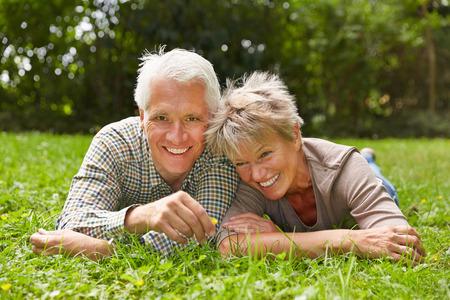 Pares mayores felices que ponen junto en la hierba en un prado