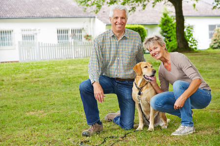 old man happy: Two smiling senior people sitting with dog in front of their house in the garden Stock Photo