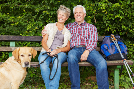 old couple walking: Senior couple with dog sitting on bench while hiking in nature