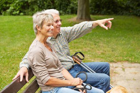 personas saludables: Pares mayores felices en banco de parque señala con el dedo en la distancia