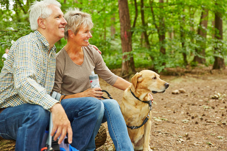 Relaxed senior couple sitting with dog in a forest during a hiking trip Stock Photo