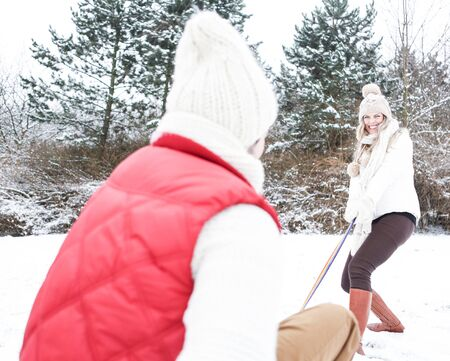 sledging people: Woman pulling man on sled in winter through snow