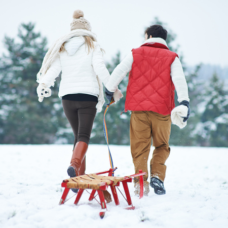 to go sledding: Couple in winter pulling a sled together through snow
