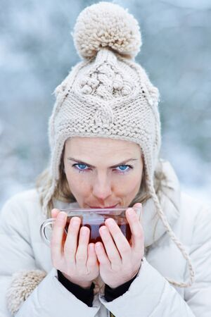 stocking cap: Woman in winter blowing in a hot cup of tea