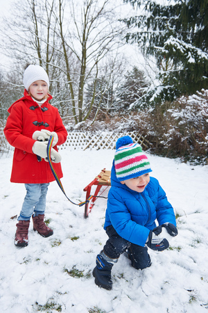 sledging people: two children with a sled playing in snow in winter