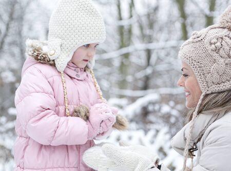 boule de neige: Heureuse m�re et la fille former une boule de neige en hiver ensemble