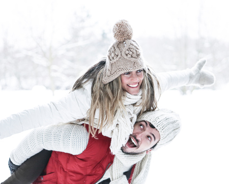 winter holiday: Happy man carrying smiling woman for piggyback ride in winter Stock Photo