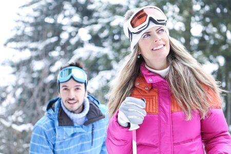 couple winter: Happy couple in winter skiing together through snow Stock Photo