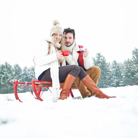 couple winter: Happy couple sitting in winter on sled and drinking tea